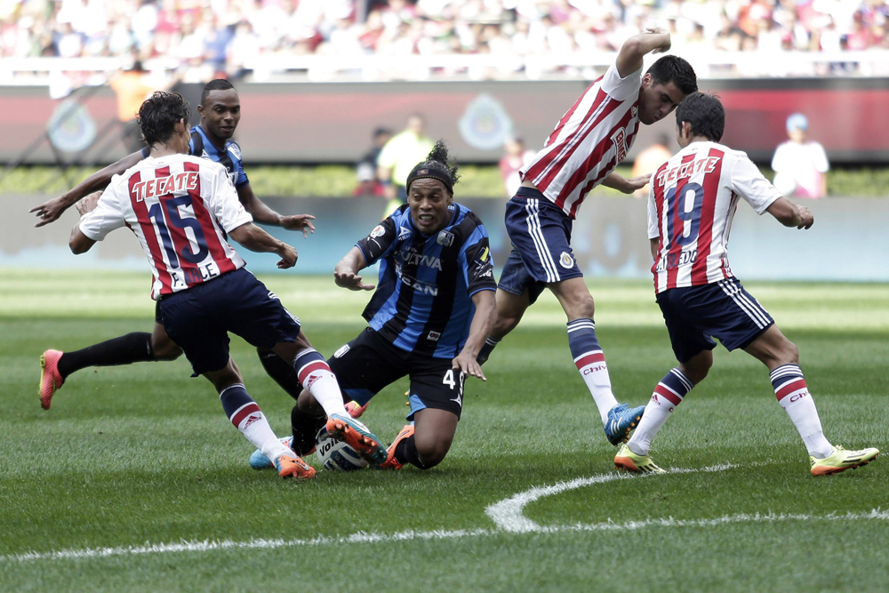Queretaro's Ronaldinho falls between Guadalajara Chivas players Arce and Toledo as he is fouled during their Copa MX soccer match in Zapopan