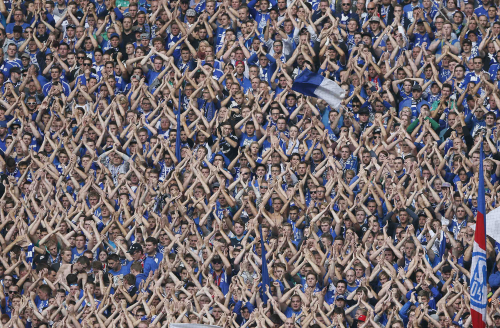 Schalke 04 supporters clap their hands to support their team in the derby against Borussia Dortmund during their German first division Bundesliga soccer match in Gelsenkirchen
