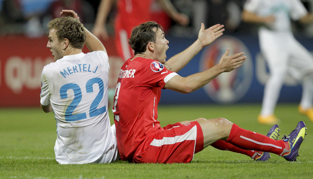 Slovenia's Mertelj and Switzerland's Lichtsteiner react during their Euro 2016 Group E qualifying match in Maribor