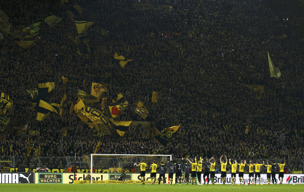 Borussia Dortmund players celebrate defeating Borussia Moenchengladbach during Bundesliga match in Dortmund