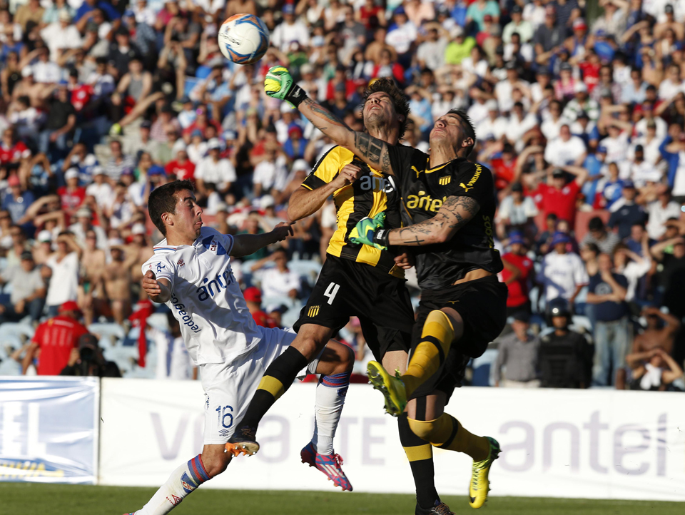 Migliore and Viera of Penarol jump for the ball with Carlos de Pena of Nacional during their Uruguayan championship match in Montevideo