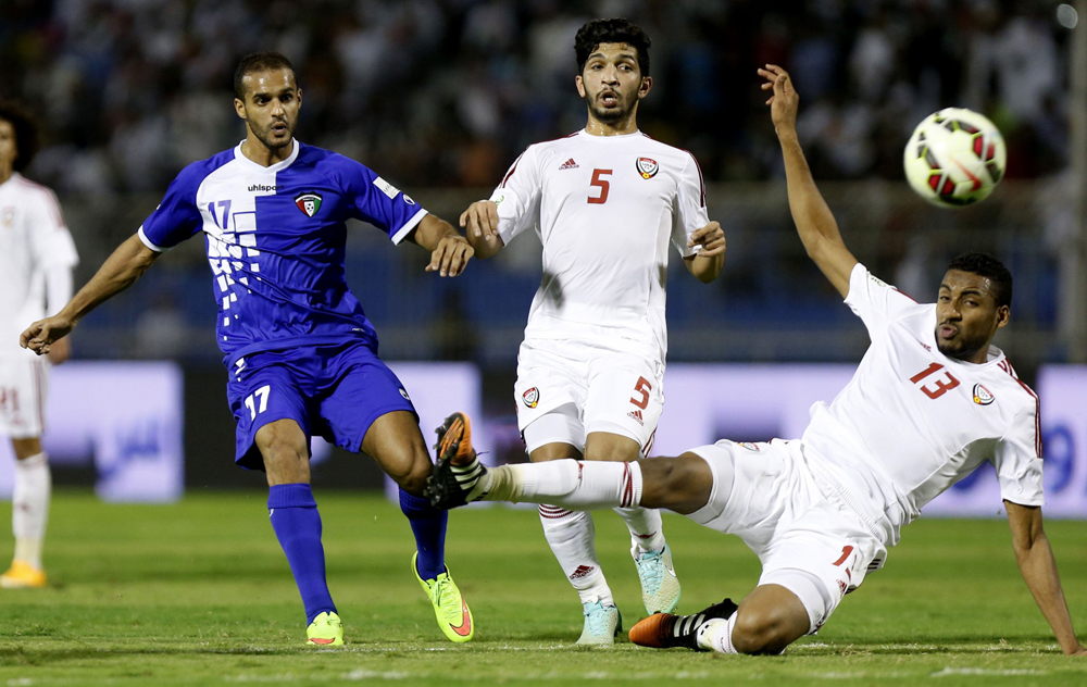 Bader AlMuttawa of Kuwait fights for the ball with Amer Al Hamadi and Khamis Ismaeil of United Arab Emirates during their Gulf Cup soccer match in Riyadh