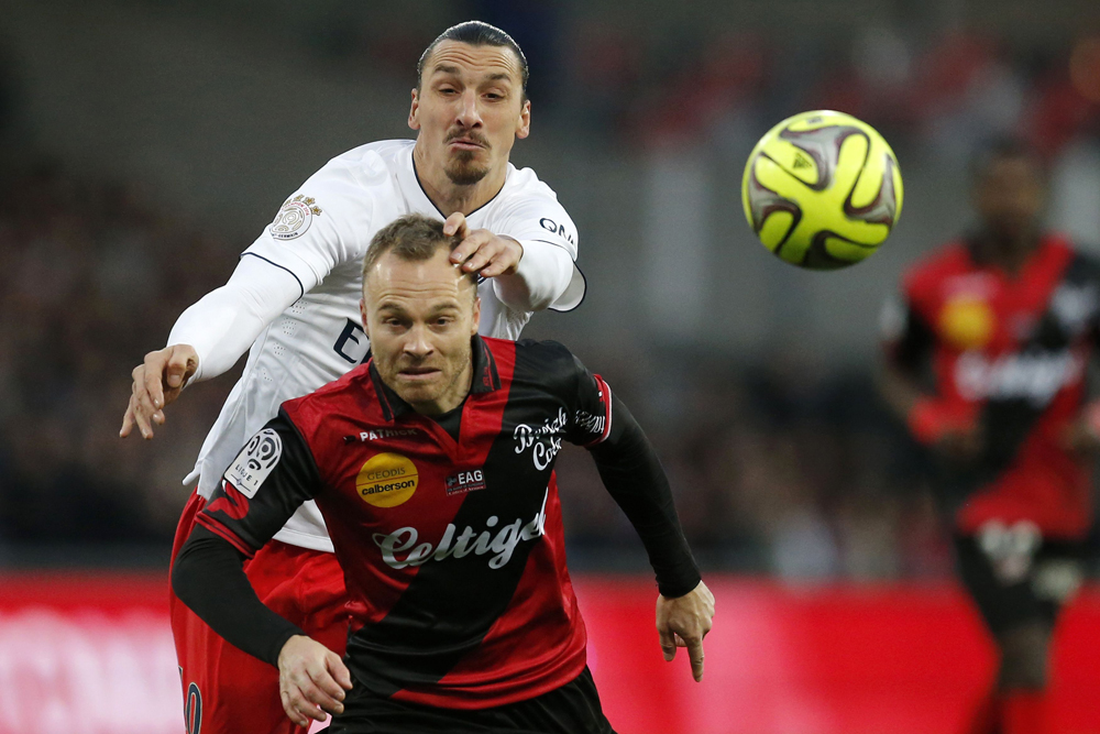 Guingamp's Jacobsen is challenged by Paris St Germain's Ibrahimovic during their French Ligue 1 soccer match at the Roudourou stadium in Guingamp