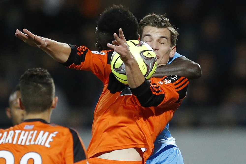 Lorient's Jeannot is challenged by Olympique Marseille's Mendy during their French Ligue 1 soccer match at the Moustoir stadium in Lorient
