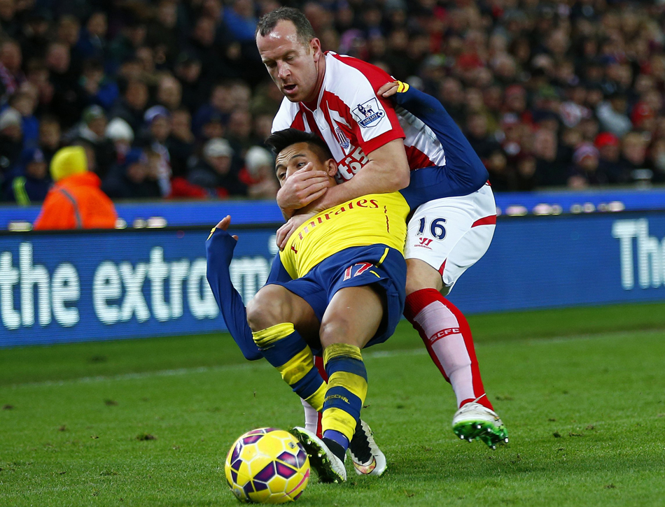 Stoke City's Charlie Adam gets a yellow card for this foul on Arsenal's Alexis Sanchez during their English Premier League soccer match in Stoke