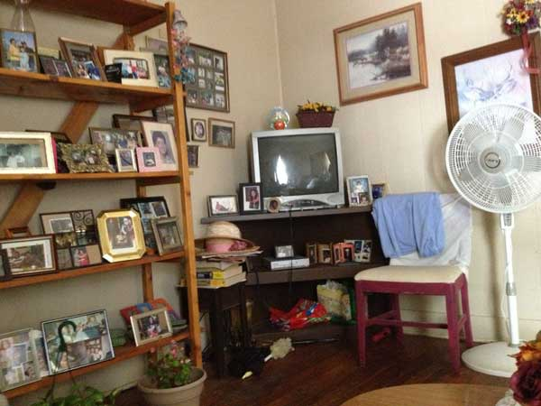 A corner of a living room with a tv, chair, fan, pictures on the wall, and a bookcase filled with framed photos