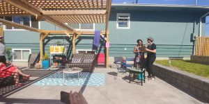 A team of two presents in the sun to a group seated on patio furniture, mostly out of view.