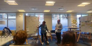 Two people stand beside a large white board where their work is mapped out with lots of arrows to indicate flow.