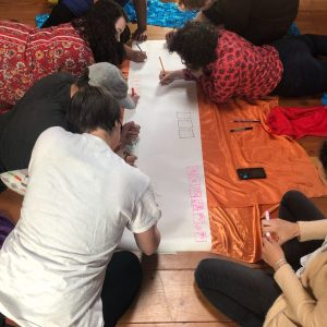 A team gathered around a a long banner of paper, on hands and knees, drawing on the floor.