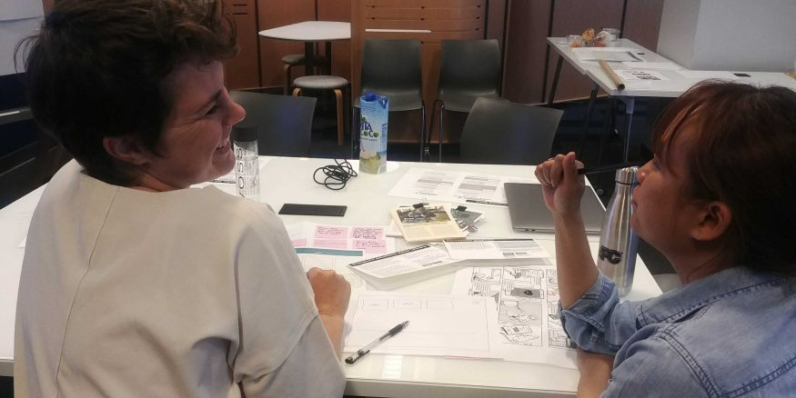 Two women sit at a desk chatting and laughing with storyboards between them.
