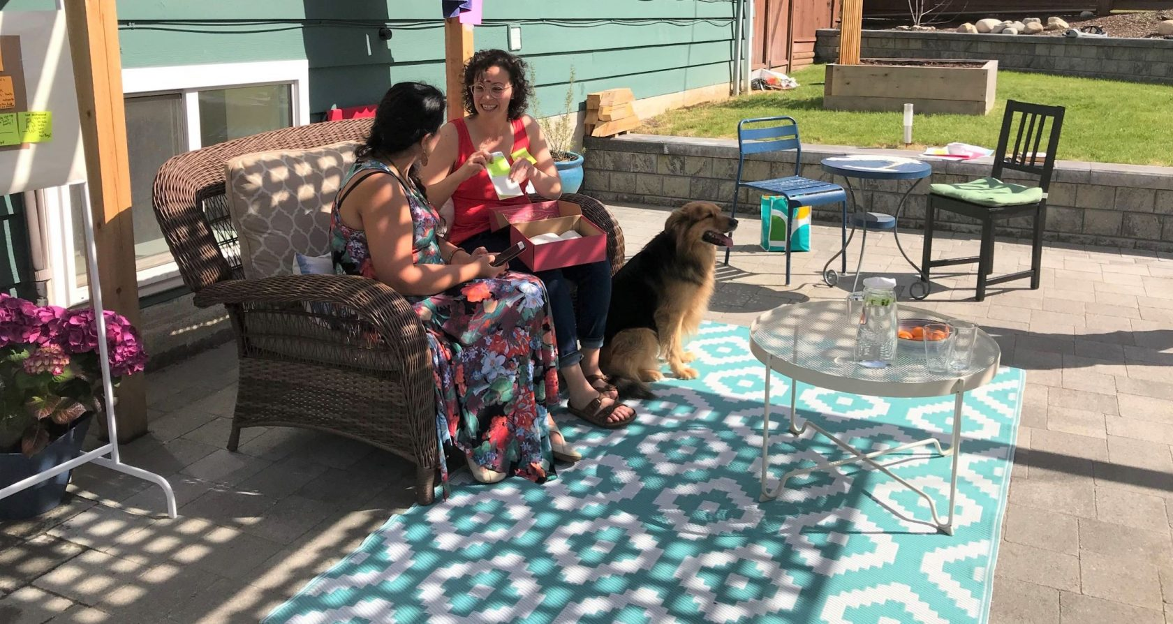 Shokhan and Alysha sit on patio furniture in dappled light below a patio arbour, accompanied by a large dog.