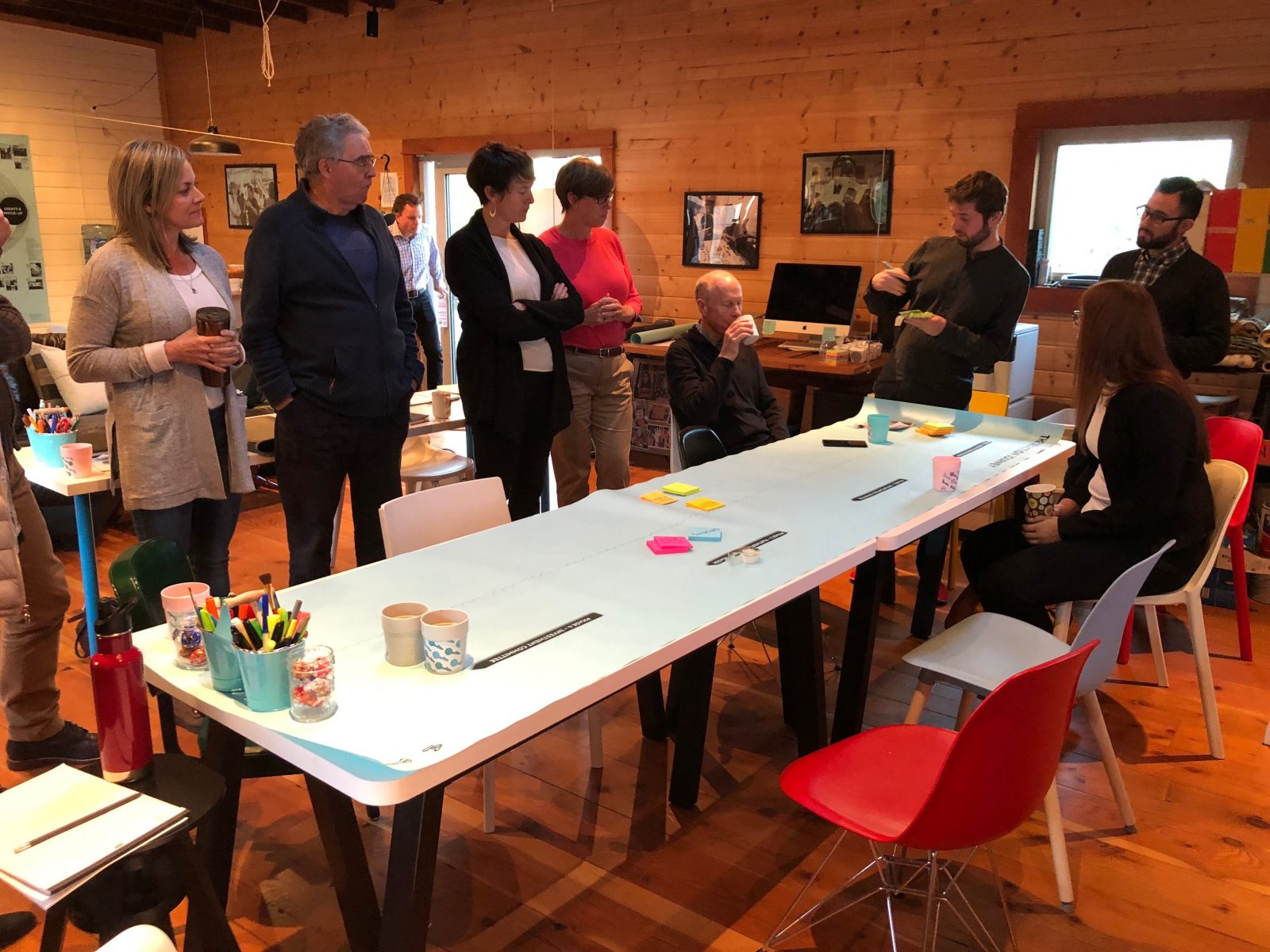 Eight adults sit and stand around a long table laid out with paper, post-its and pens.
