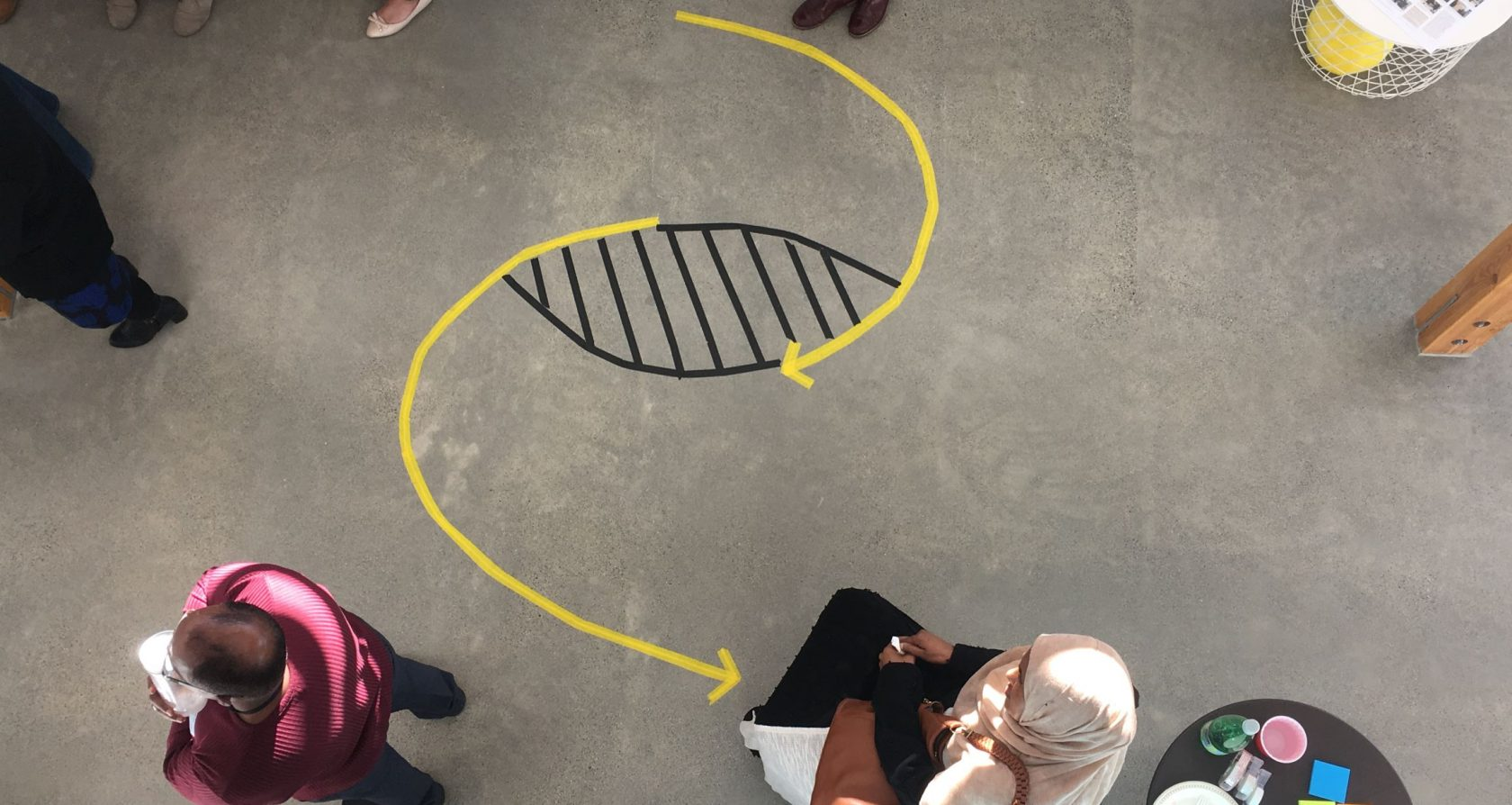A concrete floor with a taped diagram of living and dying systems (two arced arrows in an 's' like formation but with a gap in the middle of the 's' that looks like an eye. People mill about.