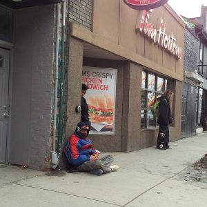 A Man in a red and black jacket and toque sits on the sidewalk in front of Tim Hortons, holding a paper cup.