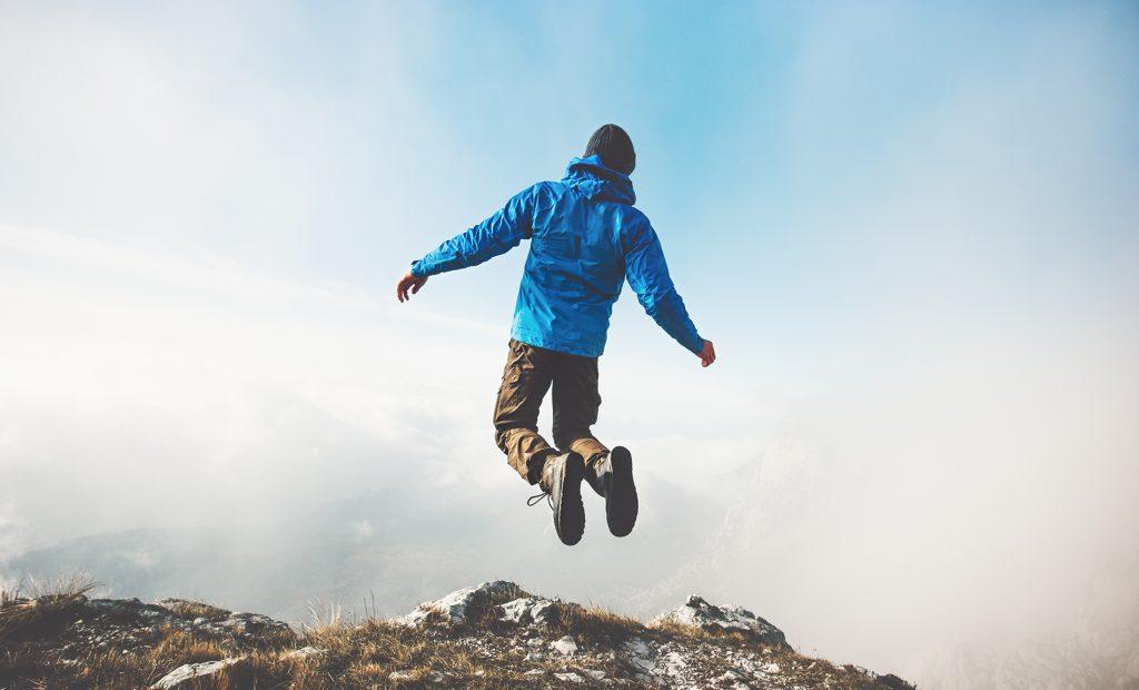 Sinitakkinen miesoletettu hyppää ilmaan sumuisessa mutta aurinkoisessa vuoristomaisemassa
