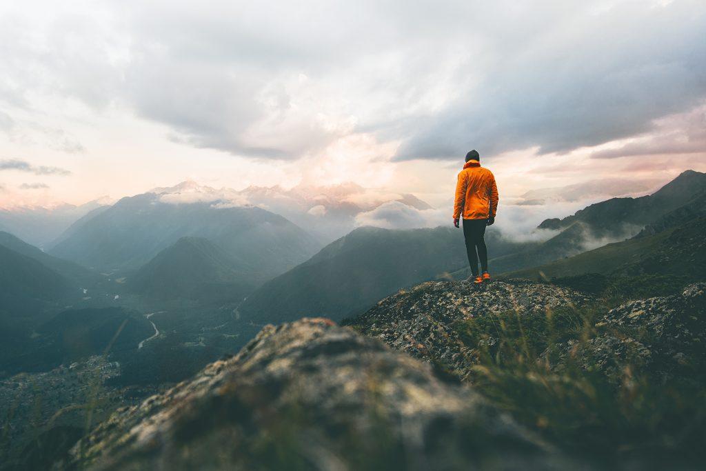 Oranssitakkinen henkilö seisoo pilviä hipovien vuorenhuippujen keskellä.