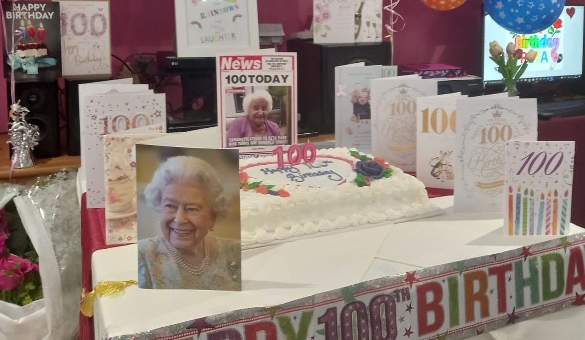 A birthday cake and a selection of cards on the table. One card is from the Queen.