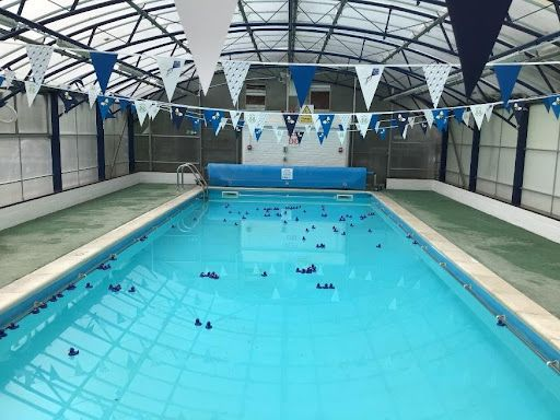 A picture of a large indoor swimming pool with blue rubber ducks in the water and blue and white bunting above on the roof.