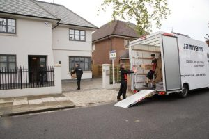 Removal men moving furniture into property