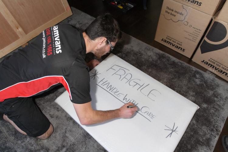 Man writing fragile sign