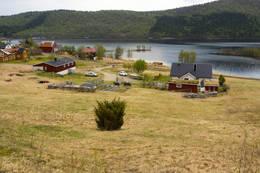 Turen starter her ved første huset i Vassbotn og går opp mellom fjøs og gult hus. - Foto: Kjell Fredriksen