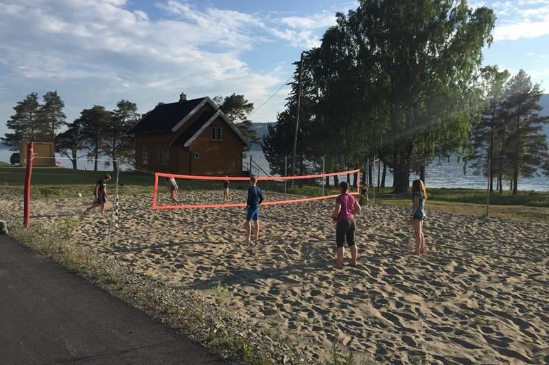Sandvolleyballbane mellom sykkelstien og hytta
