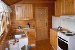 Oppholdsrom: Kjøkkenkrok med kjøleskap, komfyr og utslagsvask. Dør inn til soverom 3. - Foto: Tone Føreland