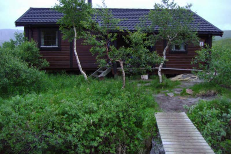 De to hyttene på stedet ligger på hver sin side av bru over bekken