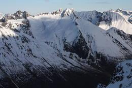 Grøtdalstindane midt i bildet, ruten starter bak klippen i forgrunnen, og går opp/ned den brede siden som vender mot venstre i bildet. -  Foto: westcoastpeaks.com/Arnt Flatmo