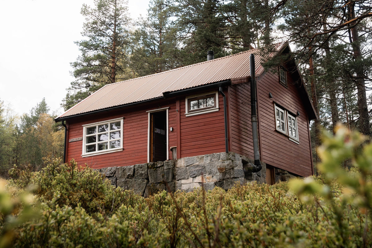 Den rødmalte hytta ligger trivelig til i skogen.