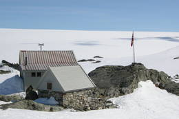 Drømmedag ved Fonnabu. Ikke et vindpust. Her ser vi steinbuen og gamlehytten og breen bak. - Foto: Pål Andersen