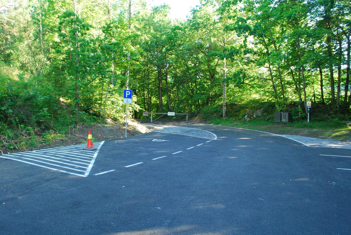 Asfaltert p-plass med HC-parkeringsplasser ca. 200 meter før gården.