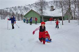 Barn har det kjempegøy i snøen utenfor Alexander Grieghytten i Bersgdalen. - Foto: Ukjent