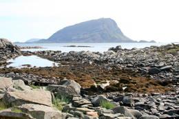 Strand under Dombefjellet. Storebatalden i bakgrunnen. - Foto: Kjartan Godø
