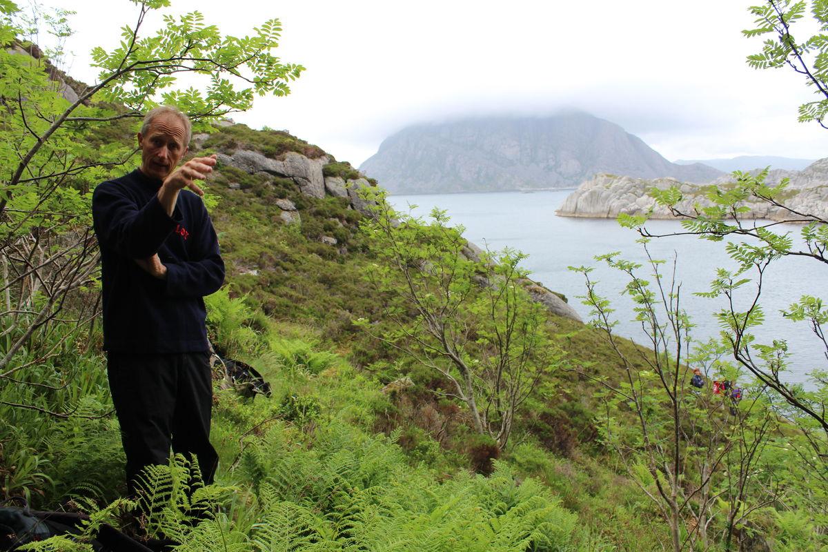 Turfolket får ei lita innføring om øyas historie. Store Batalden skimtes i det fjerne med tåkehatten på.