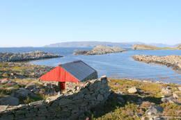 Naust i Skjelvika. Frøya-landet i bakgrunnen. - Foto: Kjartan Godø