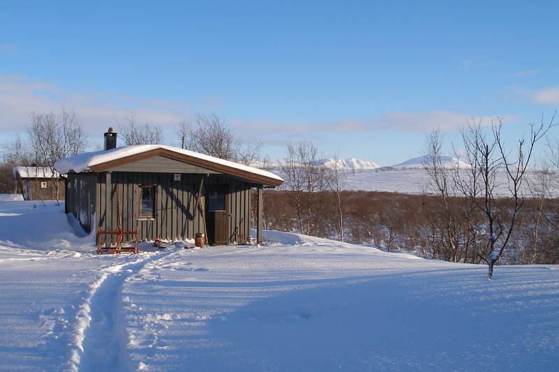 """Bojobæski, Finnmark, med Selvbetjeningshytta og """"Sikringshytta. Fjelltoppene Vuorji (1024 moh.) og Stallorassa (891 moh.) i mot nordøst."""