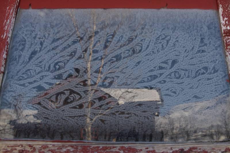 Nattefrosten laget kunstverk på glasset i utedoen, Kjennsvasshytta (Hemnes Turistforening) i speilbildet. Foto tatt i slutten av palmehelga 2012 etter flotte skiturer i eventyrlige Okstindan