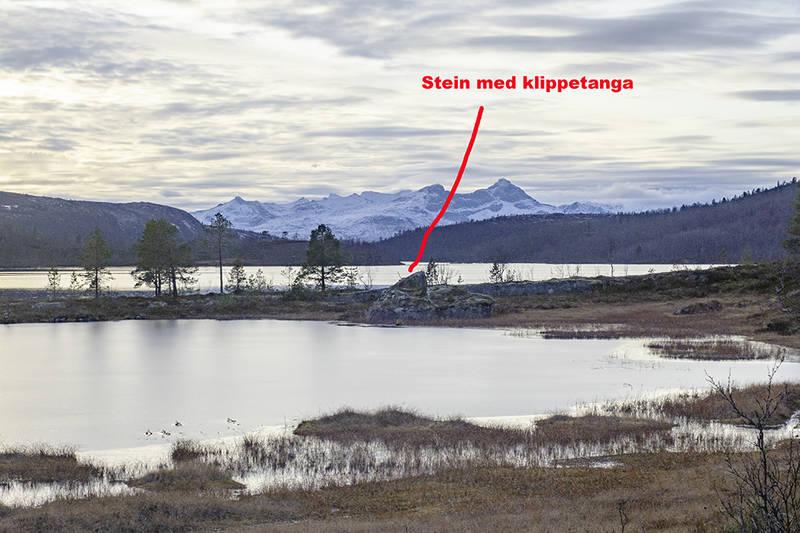 Tanga står på stein på eidet mellom tjønna og vatnet