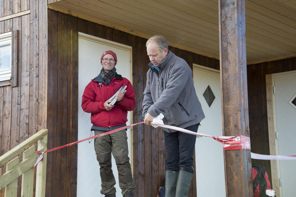 Olav Olstad klipper snora og åpner hytta. Styreleder i DNT Lillehammer, Ragnvald Jevne til venstre.