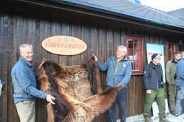 Kjetil Sudgarden og Rune Thorsen avduker Vassfarkoie skilte med ekte bjørnefell under åpningen av Vassfarkoia - Foto: Ole-Martin Høgfoss