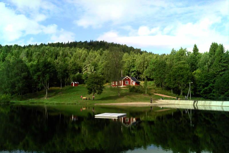 Blektjernstua og Blekktjern sett fra benk på østsida. Badebrygge midttjerns. Foto: Kristian Strømmen