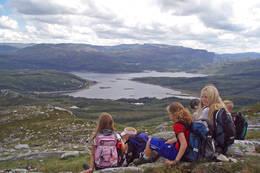 Barn på sommerleir på tur ovenfor hytten, med utsikt mot Hamlagrøvatnet. Barn på sommerleir på tur ovenfor hytten, med utsikt mot Hamlagrøvatnet.  - Foto: Bergen Turlag