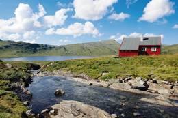 Åsedalshytten ligger sentralt i Stølsheimen, i et område som fremdeles brukes aktivt i landbruket. Omkring ligger fine stølsvoller. - Foto: Ukjent