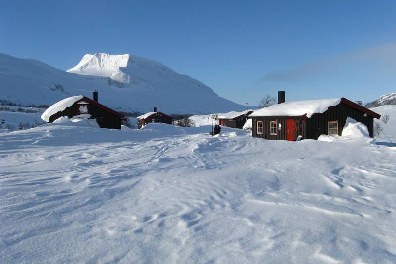 Hyttene på Rosta i Indre Troms ønsker gjestene velkommen. I bakgrunn bader Høglikka i sol.