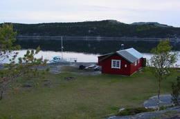 Nede ved havet kommer du til Egnarbua, der det er plass til 2-4 overnattende. Her er to robåter, ei nydelig strandeng, spennende svaberg og sandstrand.  - Foto: Svein Roald Kristiansen