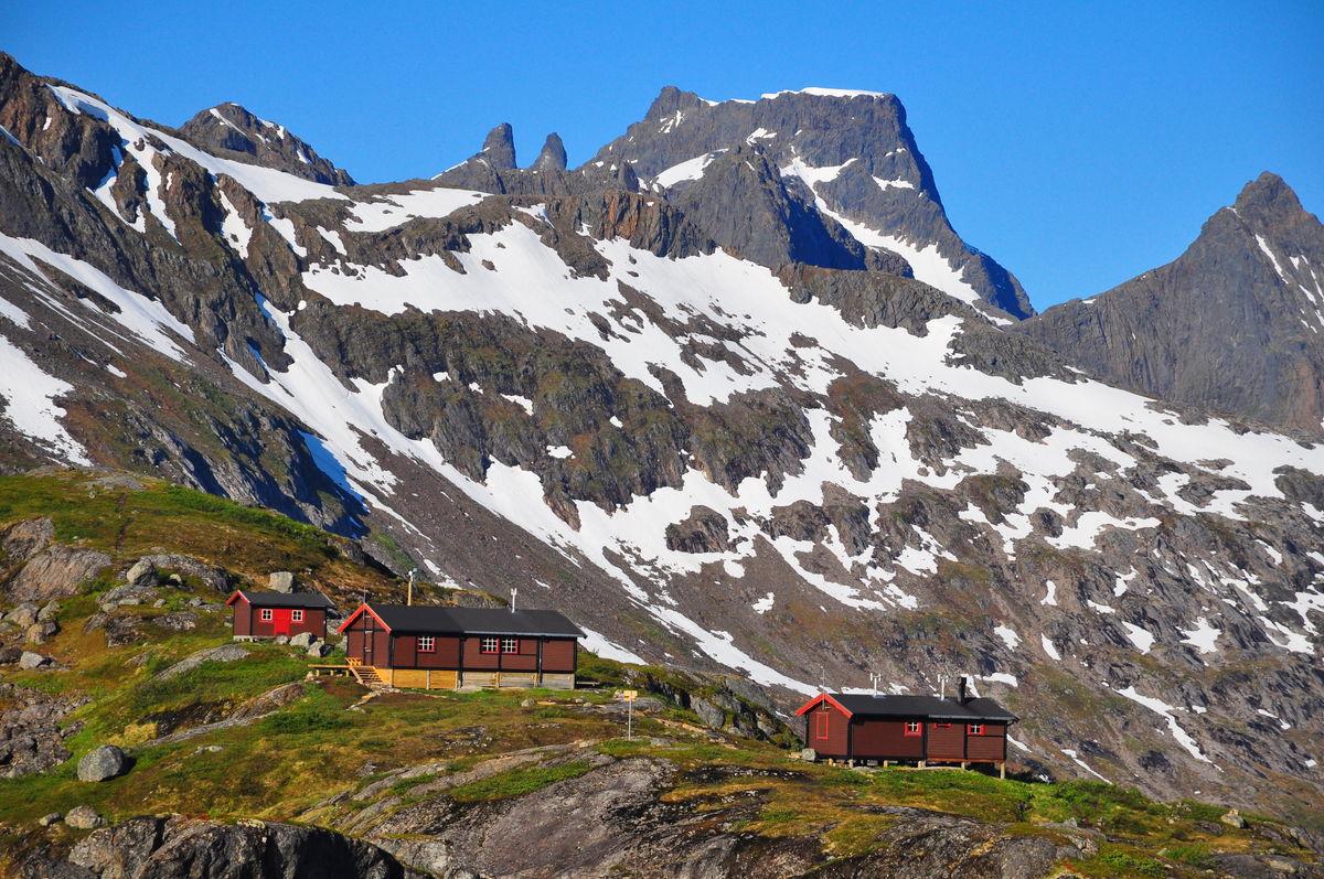 Snytindhytta, med fra venstre Uthuset, Storehytta og Lillehytta. I forgrunnen Hyttetjønna. I bakgrunnen Møyene og Møysalen.