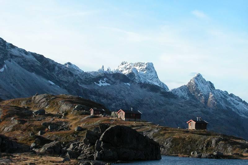 Snytindhytta, med fra venstre Uthuset, Storehytta og Lillehytta. I forgrunnen Hyttetjønna. I bakgrunnen Møyene og Møysalen. Bak til høyre Grøntinden.