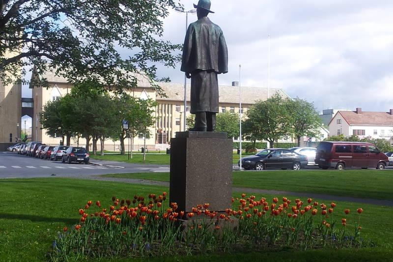 I Solparken står Komponisten Frithjof Andersen og ser mot domkirka og rådhuset.