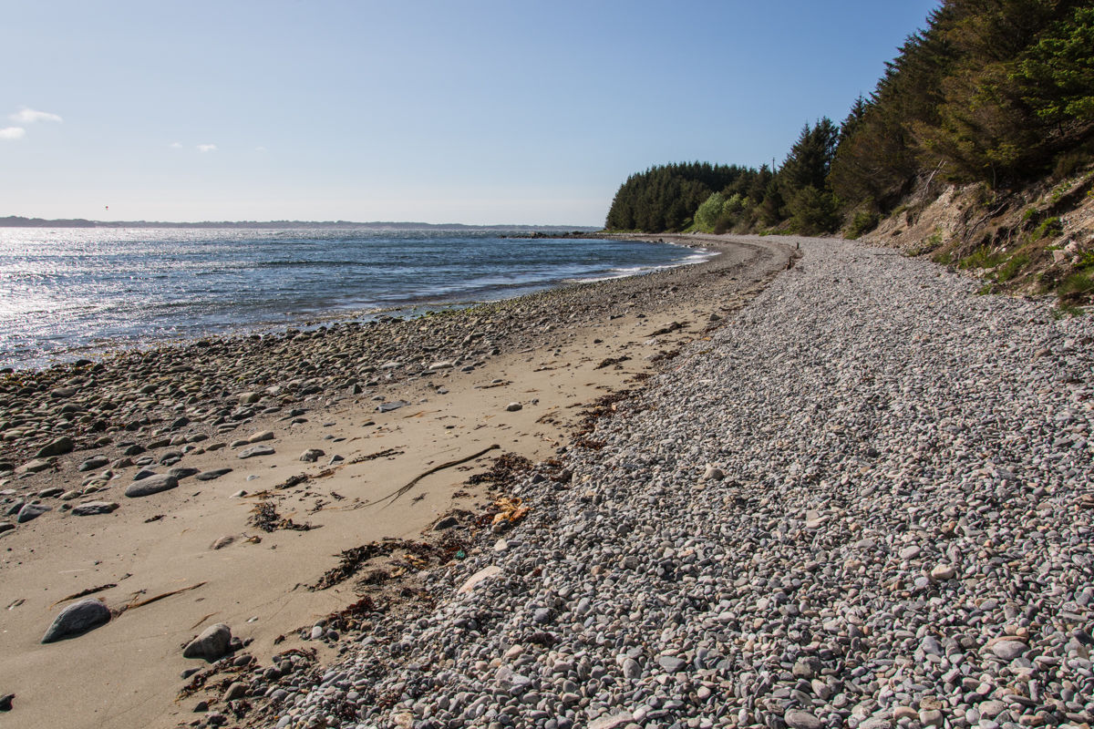 Når du går langs stranden, kan du se hvordan steinene er sortert i ulike belter.